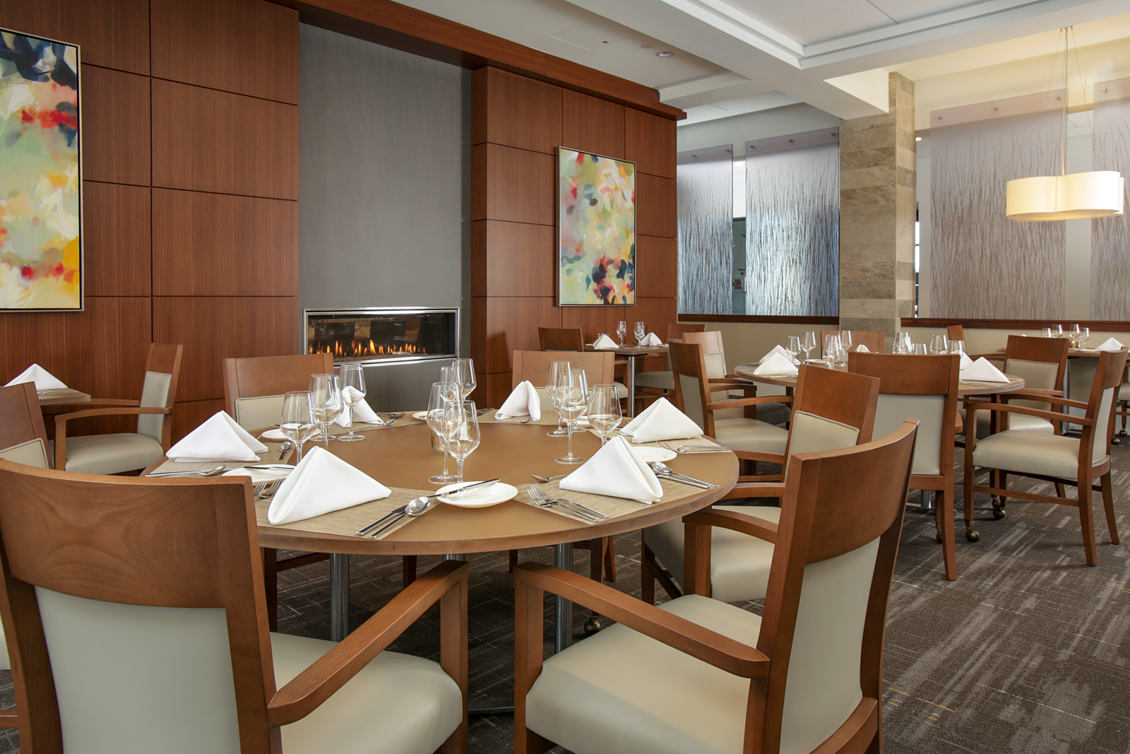 The fireplace provides a central focal point in this independent living retirement community's dining room design