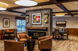 A fireplace brings the cozy to this rustic interior design of the social meeting area of an assisted living community .